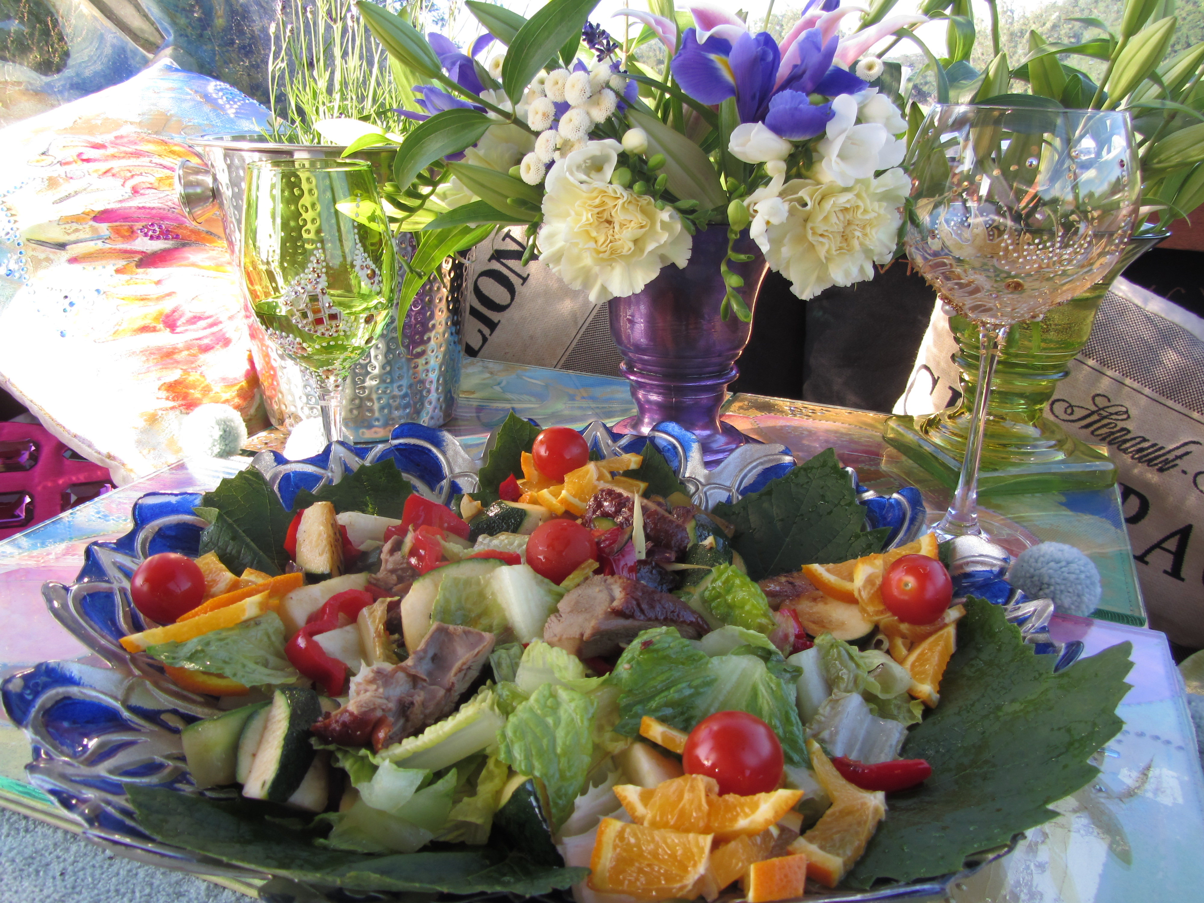 Aromatic duck salad served on vine leaves, in a decorative blue shallow glass bowl