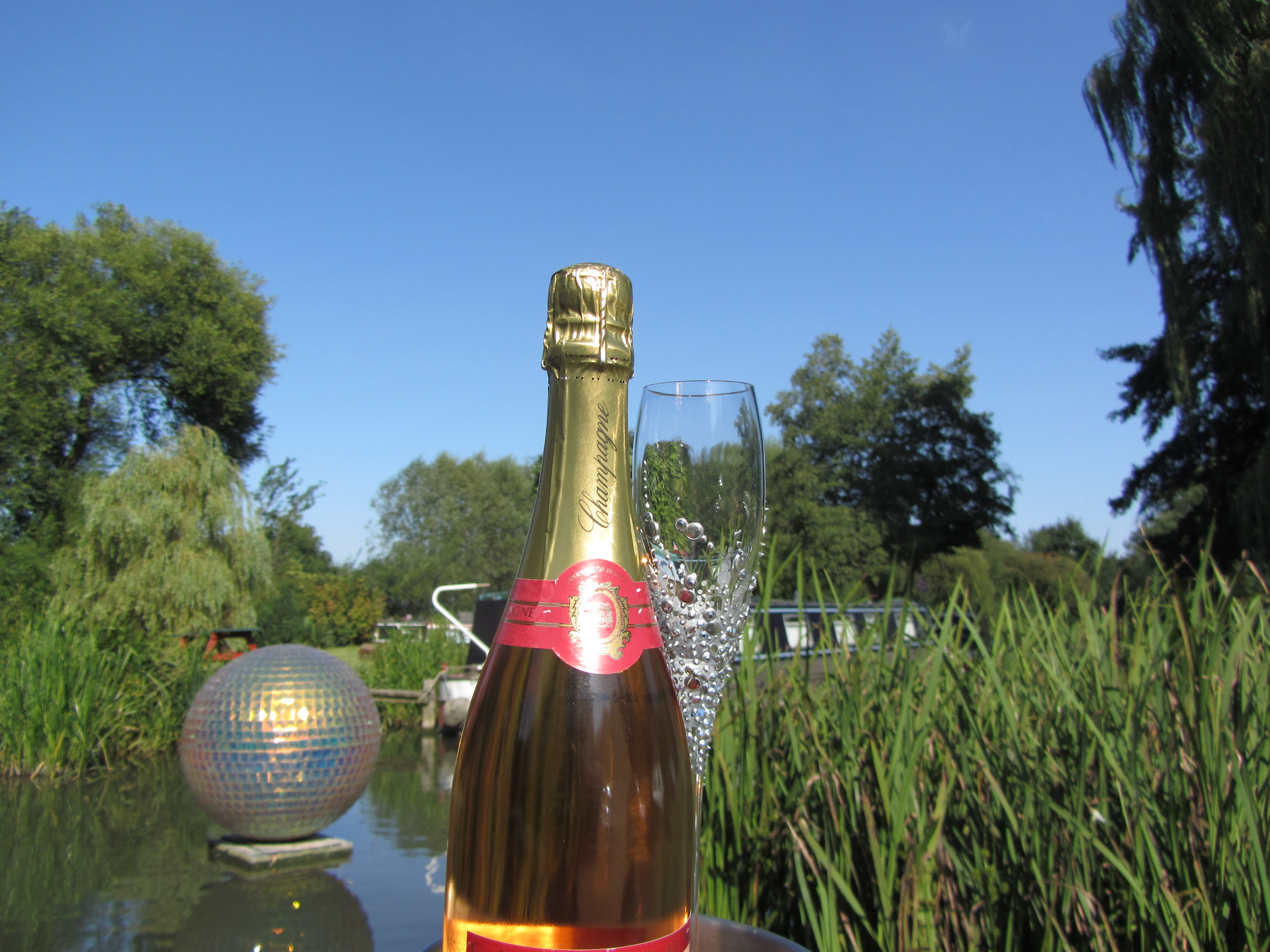 Hand decorated champagne flute and bottle of champagne with fibre glass globe artistic sculpture on the river Stort